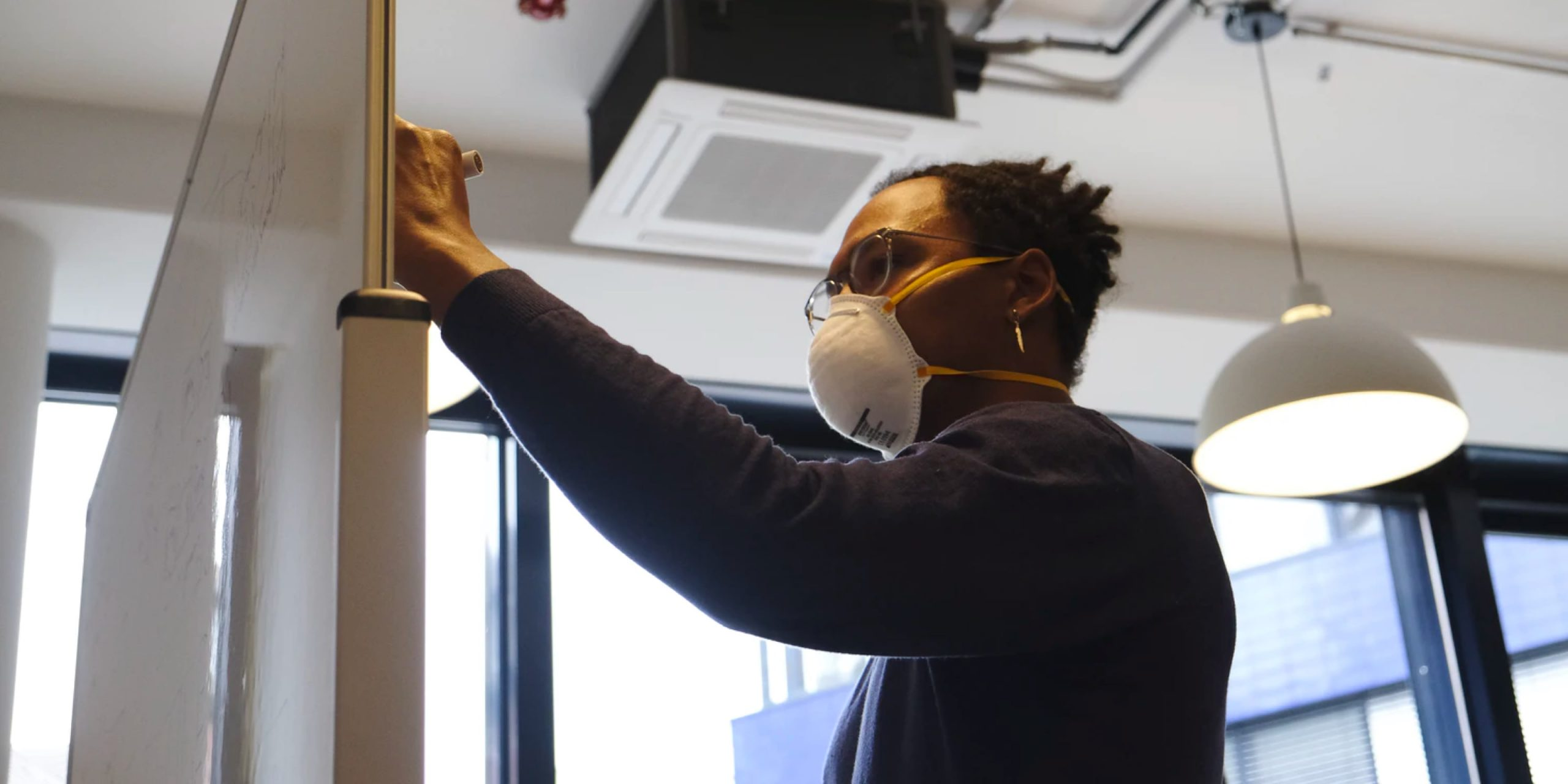 Person working on whiteboard in office space with mask on
