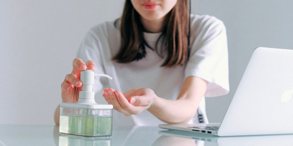 Person using hand sanitizer while sitting at a computer