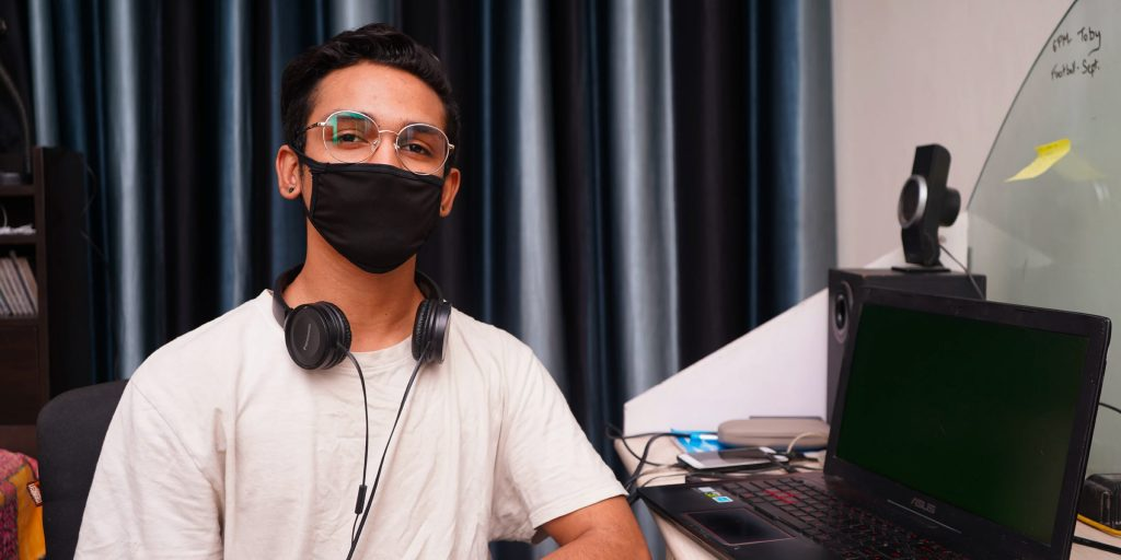 Person in semi-private workspace wearing a mask