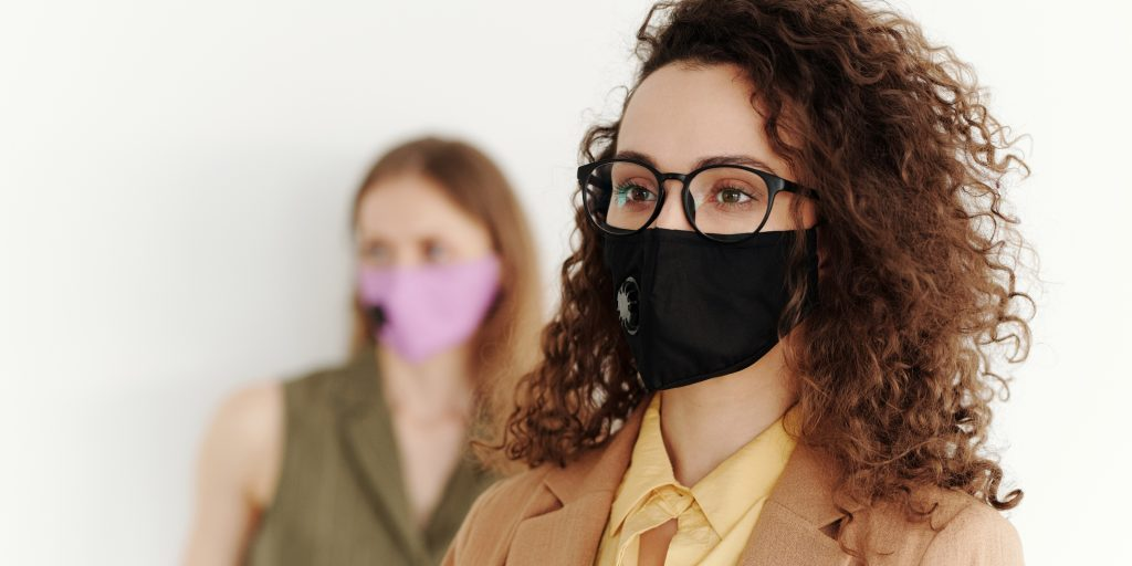 Two people wearing masks and distanced from each other in work environment