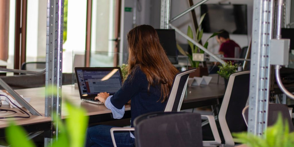 Two people working at desks in coworking space socially distanced