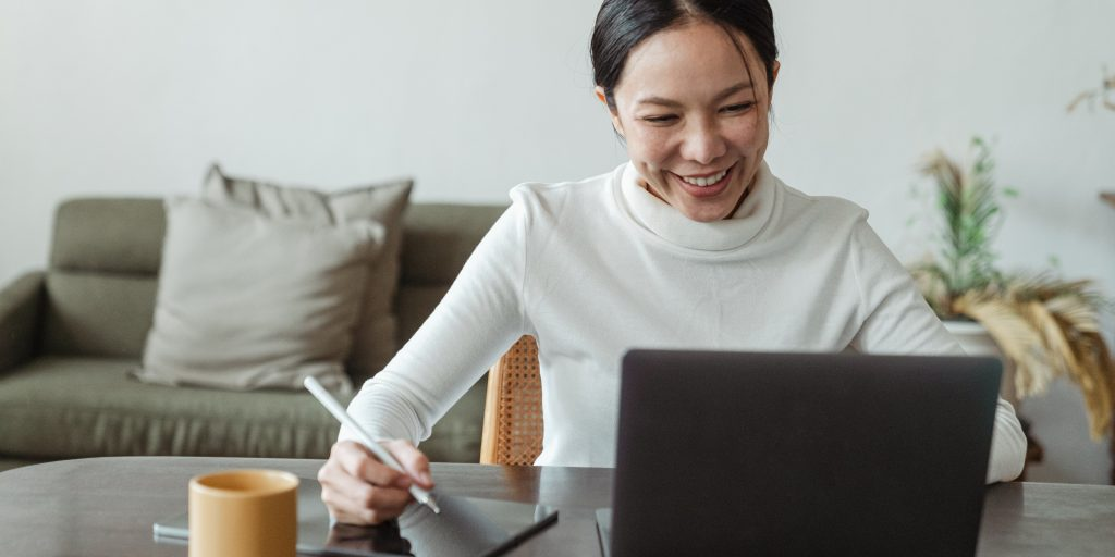 Person smiling and working from computer at home