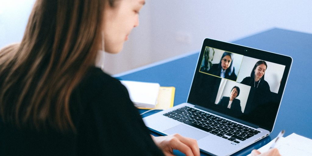 Person sitting at desk on video call with colleagues