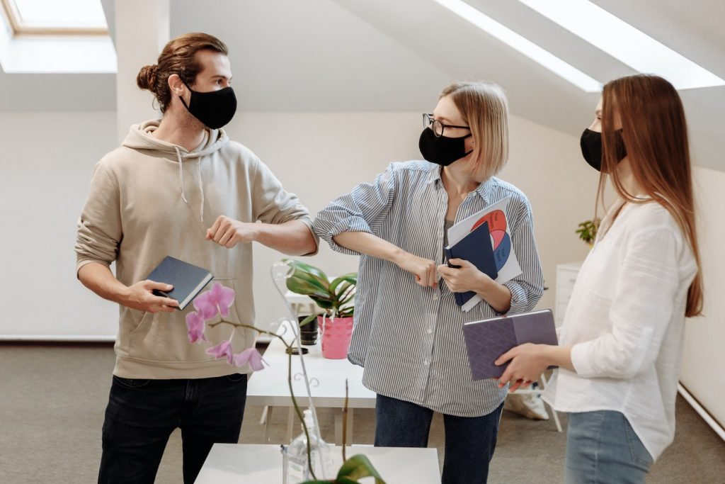 Man wearing face mask elbow bumps with female colleague at the office as another coworker looks on.