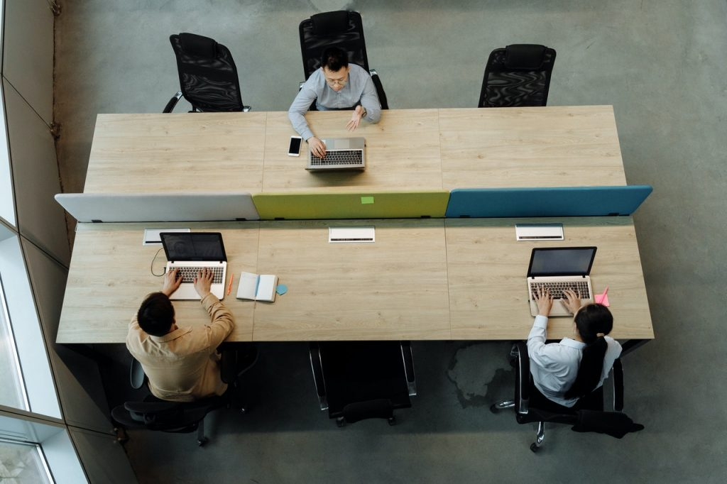 Three office workers sit at a large table. They are spaced six feet apart to maintain social distance while at work.