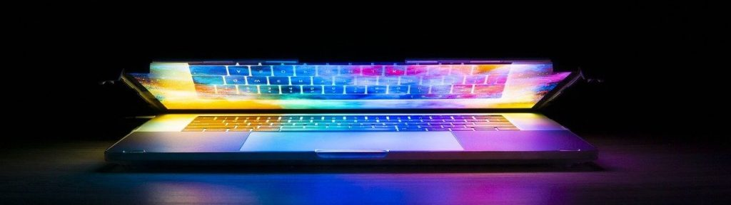 Partially open laptop against a black background. The colors coming from the laptop screen show a rainbow spectrum.