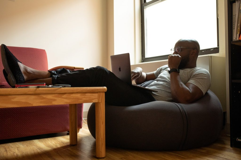 Man sits in a bean bag chair with a laptop, with his feet resting on a brown coffee table. He is working from home.