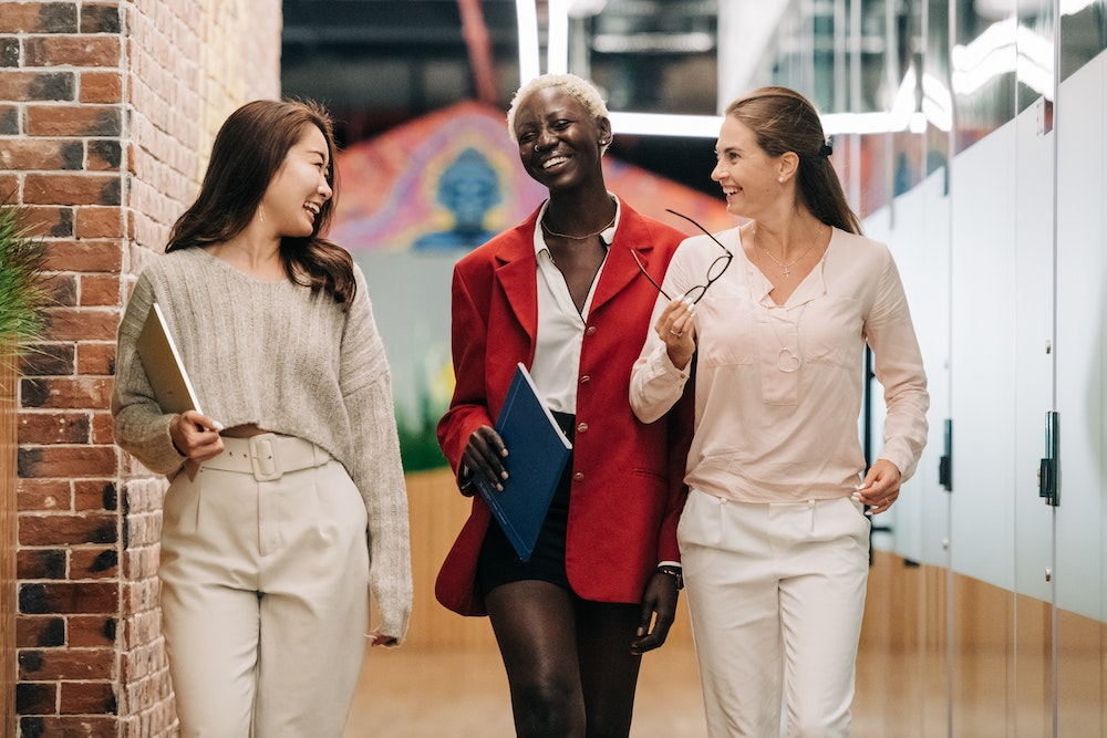 Three female colleagues smile as they walk through a coworking office with a red brick wall.