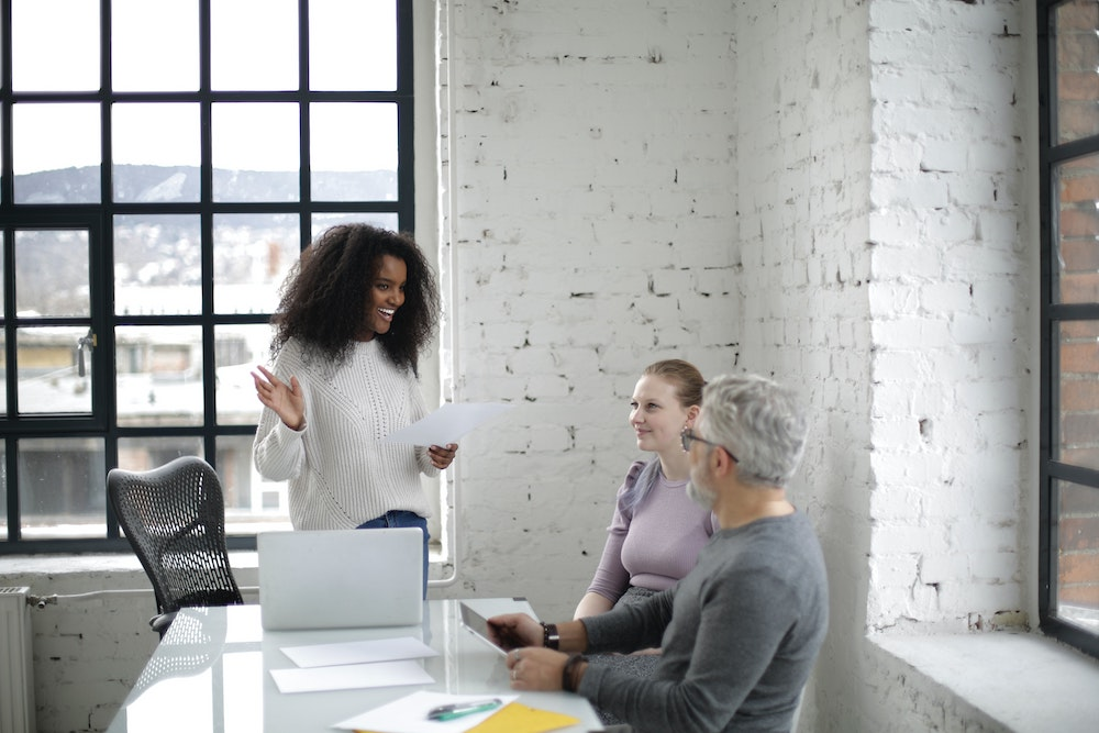 Three colleagues discuss work with a laptop at a white desk in front of a white brick wall.