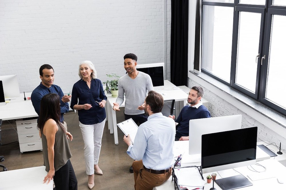 Coworking colleagues stand in a circle between white desks with computers for a daily stand up meeting.
